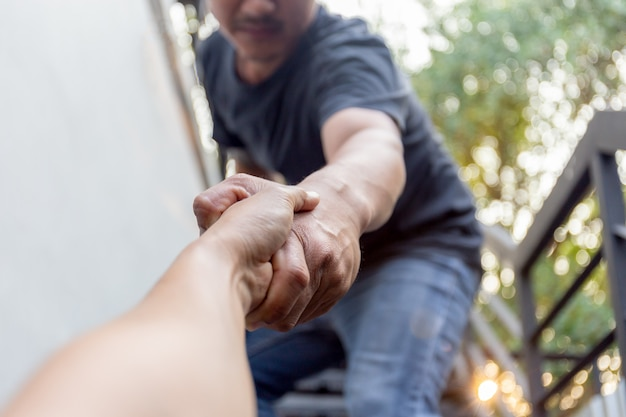 Man saving other by griping the forearm rescuing and helping concept. Premium Photo