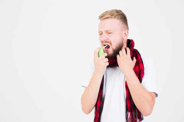Man in scarf using spray Free Photo