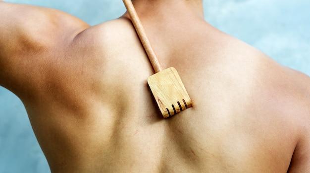Man scratching his back with a wooden backscratcher Premium Photo