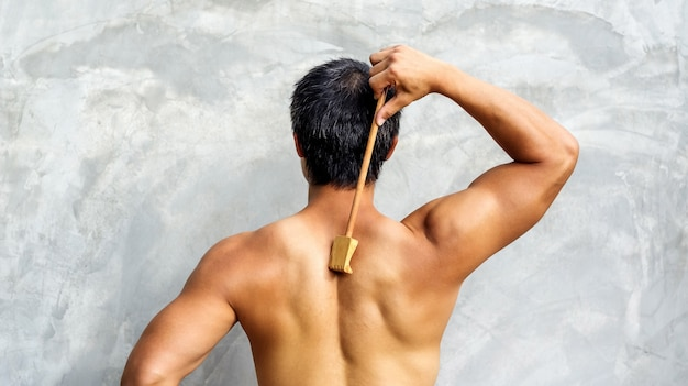 Man scratching his back with a wooden backscratcher Premium Photo