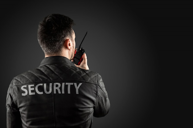 The man, security, is holding a walkie-talkie. Premium Photo