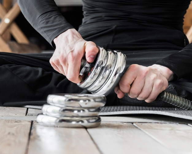 Man setting up discs for dumbbell Free Photo