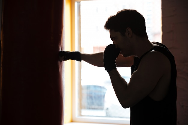 Man in shadow kicking the punching bag Free Photo