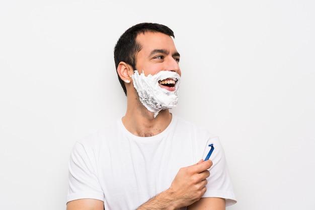 Man shaving his beard happy and smiling Premium Photo