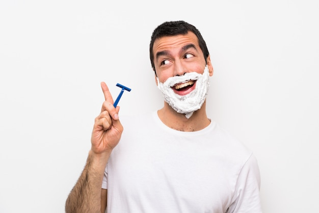 Man shaving his beard over isolated white background intending to realizes the solution while lifting a finger up Premium Photo