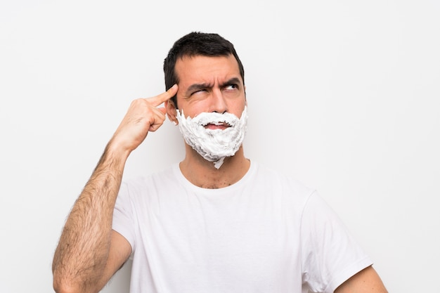 Man shaving his beard over isolated white  having doubts and thinking Premium Photo