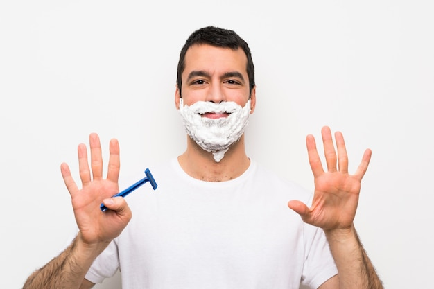 Man shaving his beard over isolated white wall counting nine with fingers Premium Photo