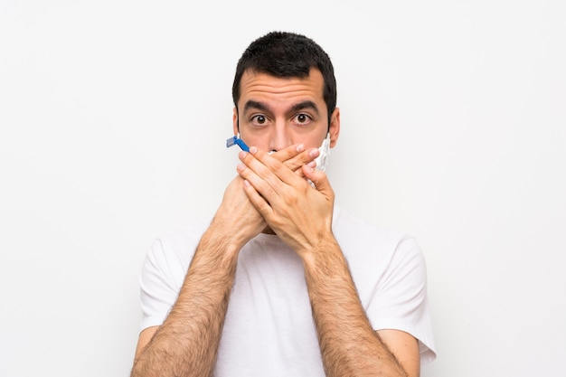 Man shaving his beard over isolated white wall covering mouth with hands Premium Photo