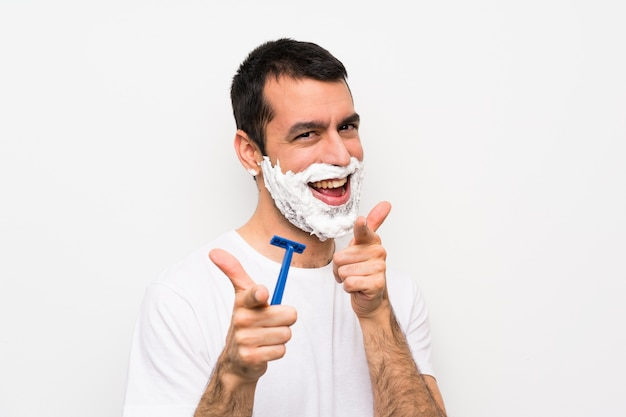 Man shaving his beard over isolated white wall pointing to the front and smiling Premium Photo
