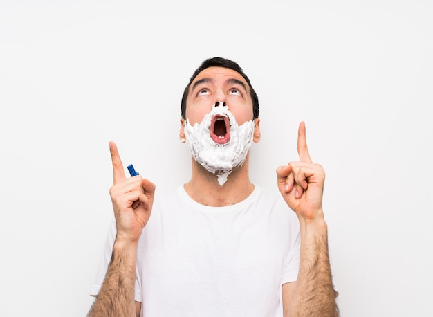 Man shaving his beard over isolated white wall surprised and pointing up Premium Photo