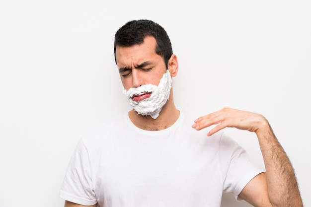 Man shaving his beard with tired and sick expression Premium Photo