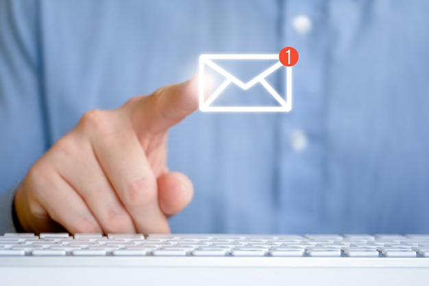 A man in a shirt in front of the keyboard. abstract email icon with new message. internet feedback concept. Premium Photo