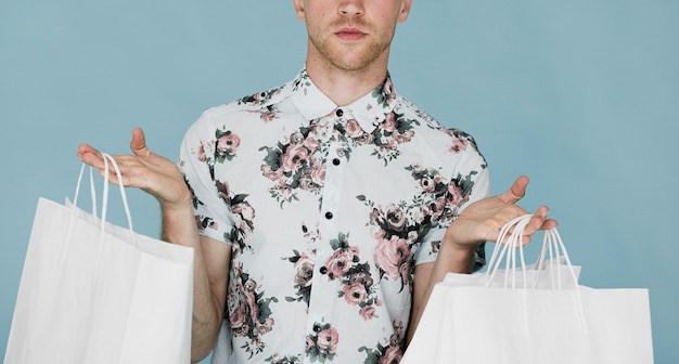 Man in shirt holding shopping bags in both hands Free Photo