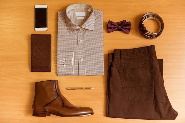 Мужская рубашка, брюки, галстук-бабочка, пояс, обувь и мобильный телефон. Premium Фотографии