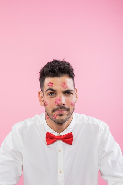 Man in shirt with lipstick kiss marks on face Free Photo