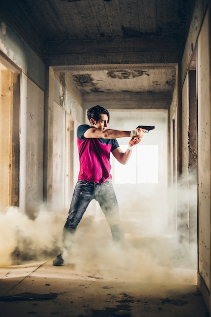 Man shooting with a gun in a ruined building in a steam Free Photo