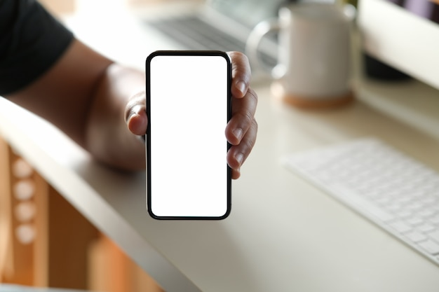 Man showing blank screen mobile phone at office Premium Photo