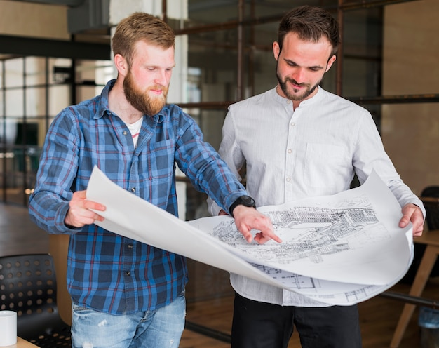 Man showing blue print to his colleague at office Free Photo