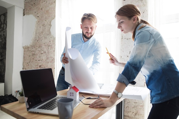 Man showing blueprint to his female colleagues at workplace Free Photo
