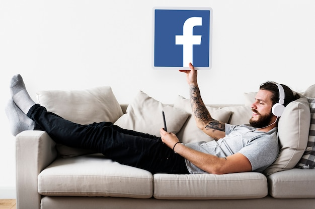 Man showing a facebook icon Free Photo