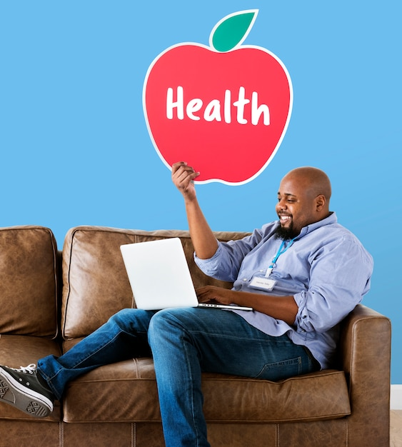 Man showing healthy apple icon on couch Free Photo