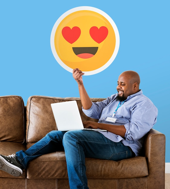 Man showing heart eyes emoticon on couch | Free Photo