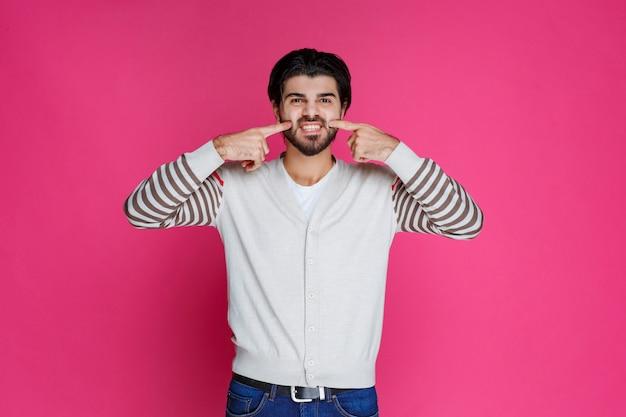 Poingint指で彼の歯を示す男。 無料写真