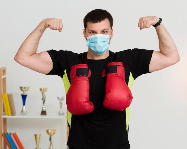 医療マスクを着用しながら彼の筋肉を披露する男 無料写真