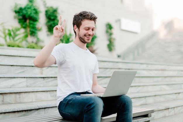 Man showing peace gesture to laptop webcam Premium Photo