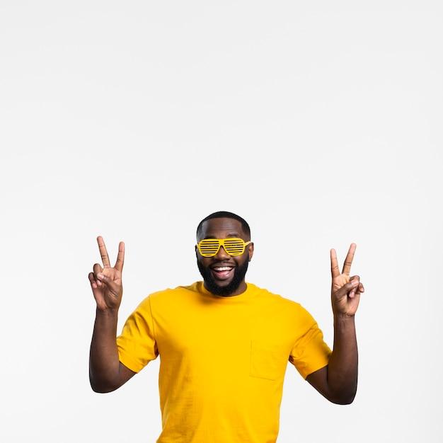 Uomo che mostra il segno di pace Foto Gratuite