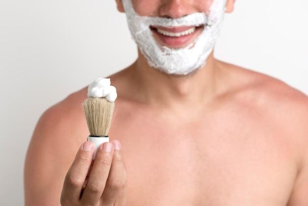 Человек показывает кисточку для бритья с пеной во время бритья Бесплатные Фотографии