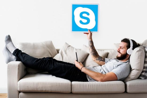 Uomo che mostra un'icona di skype Foto Gratuite