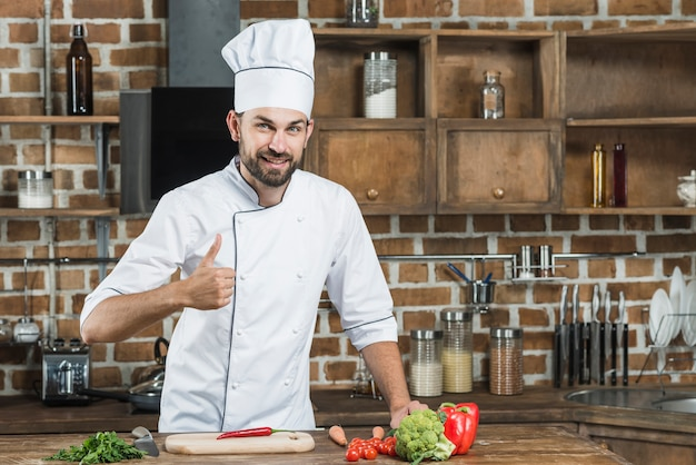 Man showing thumb up sign standing behind the kitchen counter with vegetables Free Photo