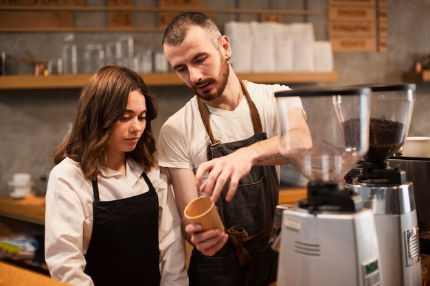 Man showing woman a cup with coffee machine Free Photo
