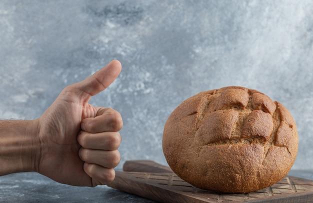 남자는 호밀 빵 한 덩어리까지 엄지 손가락을 보여줍니다. 고품질 사진 무료 사진