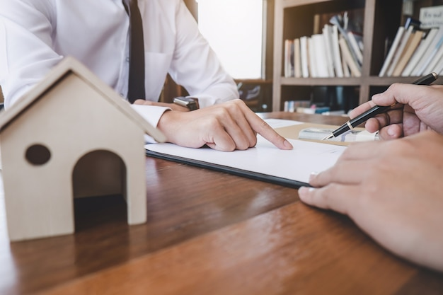 Man sign a home insurance policy on home loans, insurance agent analyzing about home investment loan Premium Photo
