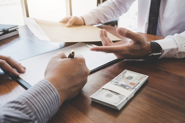 Man sign a home insurance policy on home loans, insurance agent analyzing investment Premium Photo