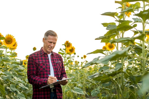 Man signing on a clipboard in a field Free Photo