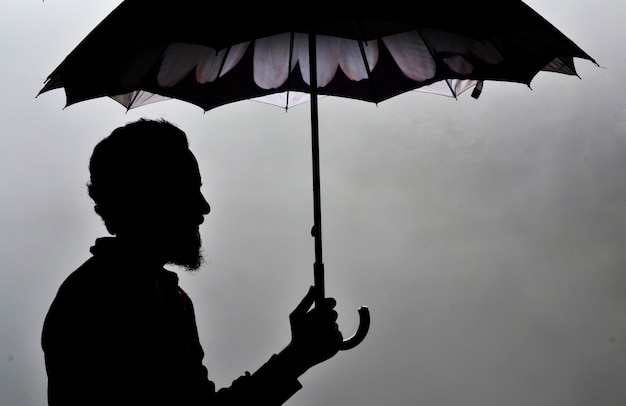 man silhouette holding an umbrella photo free download