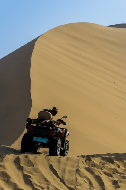 Man sit on the quad bike in gobi desert with dunes background in dunhuang, china Premium Photo