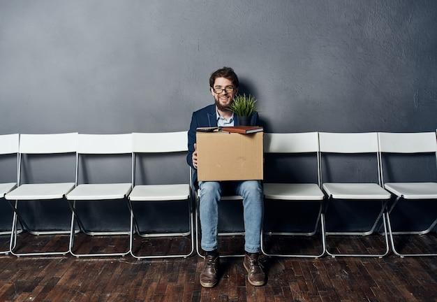 Мужчина сидит на стуле с вещами, отклоняющими депрессию от недовольства Premium Фотографии