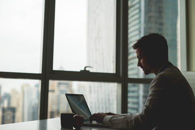 壮大な街の景色を望むパノラマの窓の横にあるテーブルに座っている男。 Premium写真