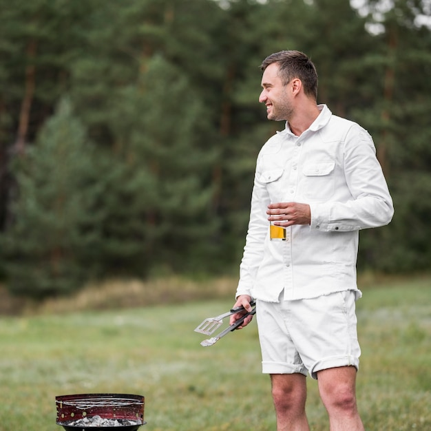 Man sitting next to barbecue and having a beer Free Photo