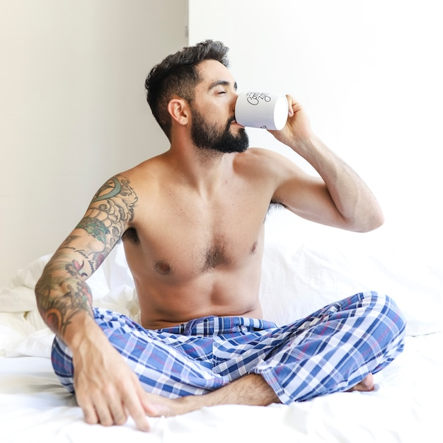 Man sitting on bed drinking coffee Free Photo