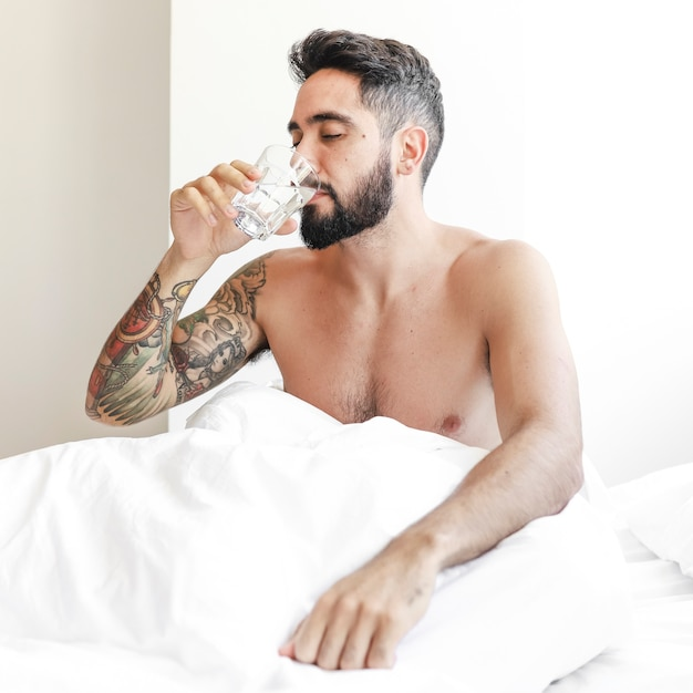 Man sitting on bed drinking glass of water Free Photo