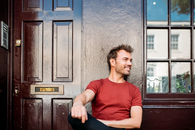 Man sitting in a bench on a beautiful maroon background Premium Photo
