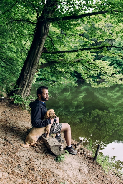 Man sitting on the bench with the dog by the lake Premium Photo