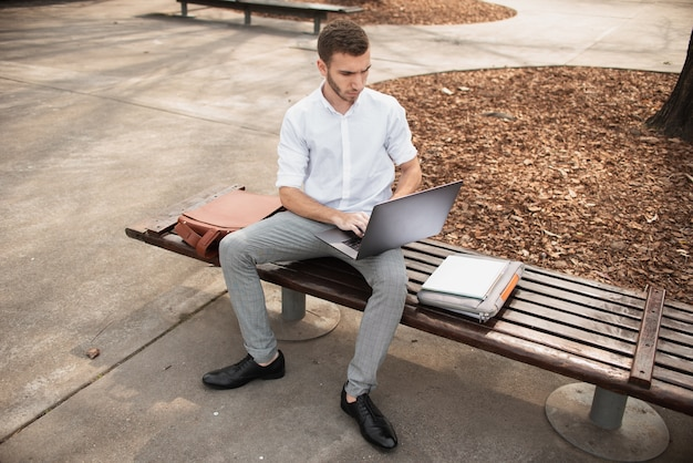 Man sitting on bench and working on laptop Free Photo