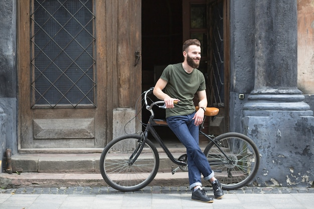 Man sitting on bicycle in front of an open door Free Photo