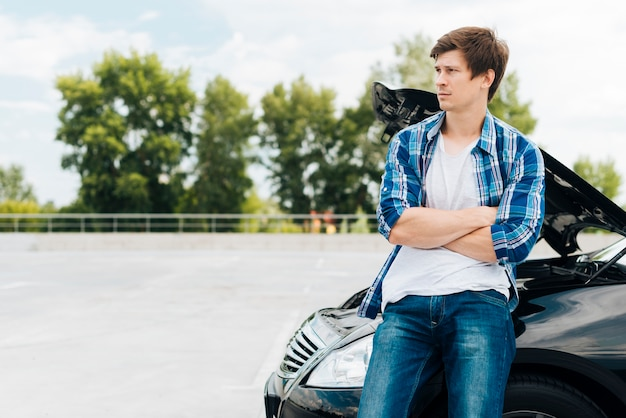 Man sitting on car with copy space Free Photo
